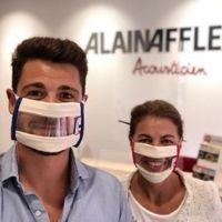 Selfie d'un jeune homme et d'une jeune femme portant des Masques Sourire devant un mur affichant le logo Alain Afflelou Acousticien