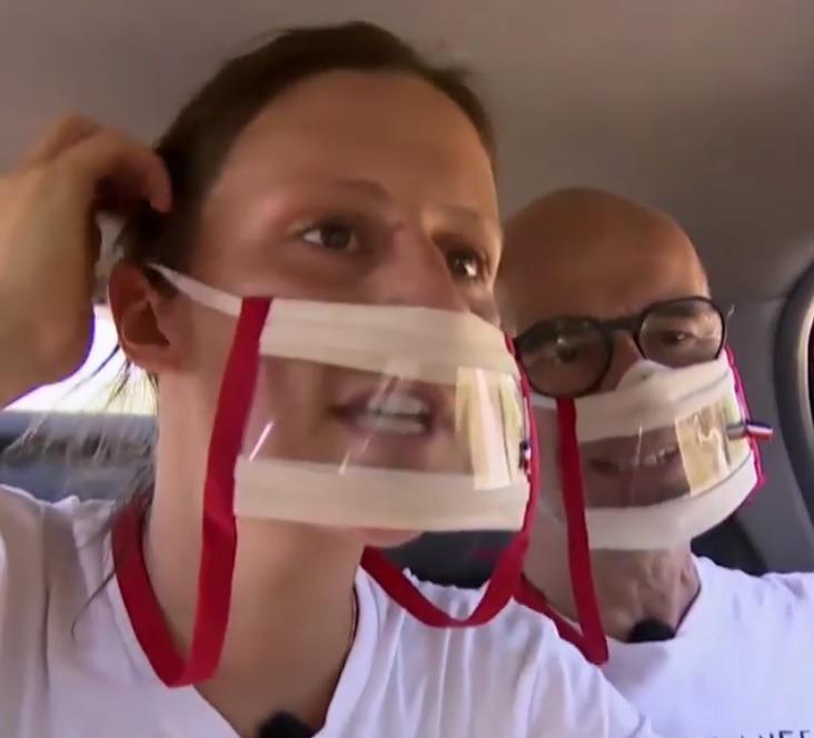 Photo de Christophe et Claire le duo père fille de Pékin Express ici dans une voiture pendant l'émission. On les voit porter des masques sourire rouge d'Odiora