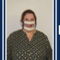 Photo d'une jeune femme portant un masque transparent sourire pour permettre la lecture labiale