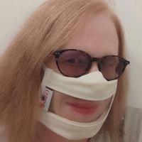 Selfie d'une femme âgée portant des lunettes de soleil et un Masque Sourire permettant de laisser voir son rouge à lèvres