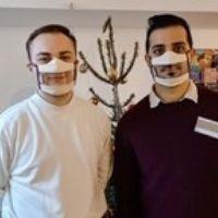 Photo de deux jeunes hommes portant des Masques Sourire devant un sapin de Noël
