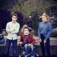 Photo d'un jeune homme en fauteuil roulant accompagné d'un autre jeune homme et d'une jeune femme, tous les trois portant des Masques Sourire